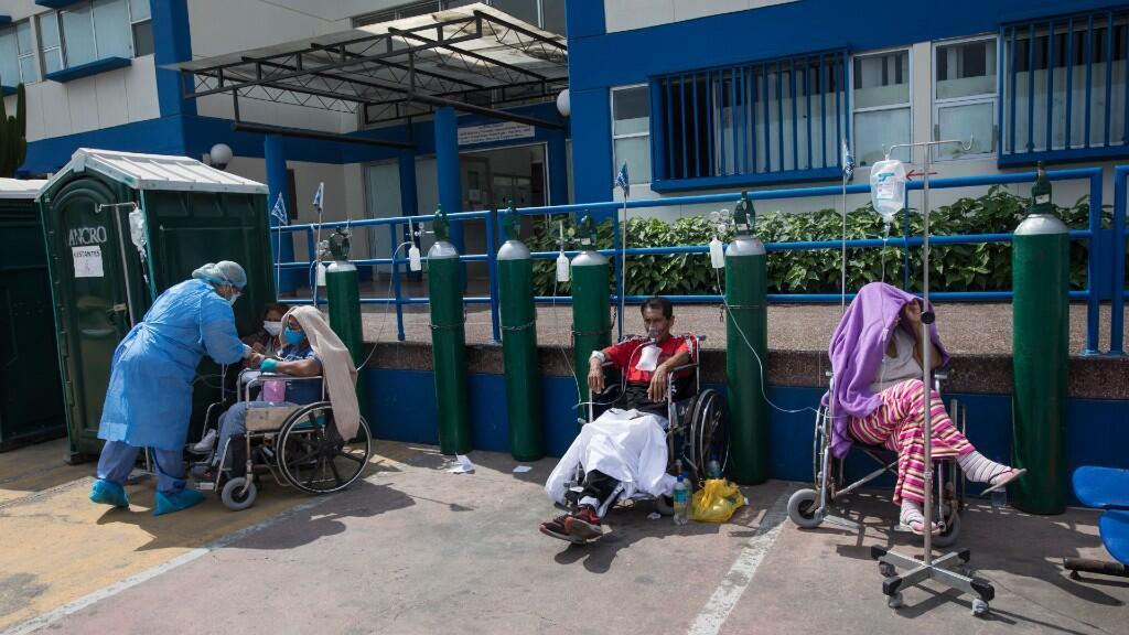 Personas contagiadas por Covid-19 esperan en fila a una cama libre en los exteriores de un hospital de Lima, en Perú. 30 de abril de 2020.