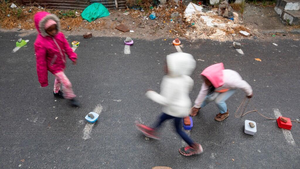 Niños sudafricanos marcan sus lugares en una fila para recibir alimentos, en medio de las medidas de distanciamiento social para tratar de mitigar el brote del Covid-19. En Ciudad del Cabo, Sudáfrica, el 28 de mayo de 2020.