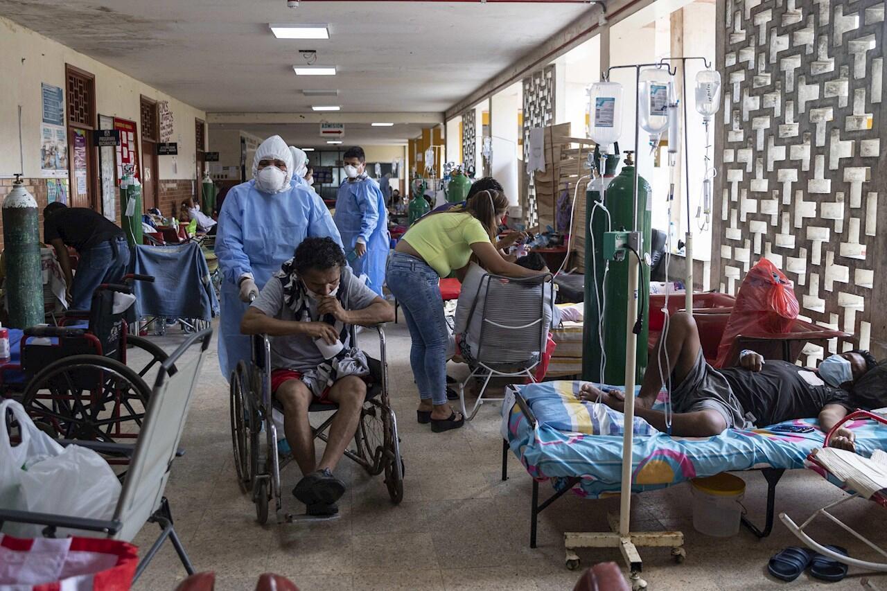 Un médico con traje de bioseguridad es registrado al movilizar a un paciente en silla de ruedas en una sala con pacientes de Covid-19, en el Hospital Regional de Iquitos, en Iquitos (Perú).