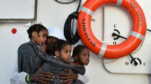 Un père tient dans ses bras ses filles. Ils ont été sauvés en Méditerranée, le 24 mai 2016.