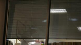 محقق يفتش داخل مكاتب كامبريدج أناليتيكا.