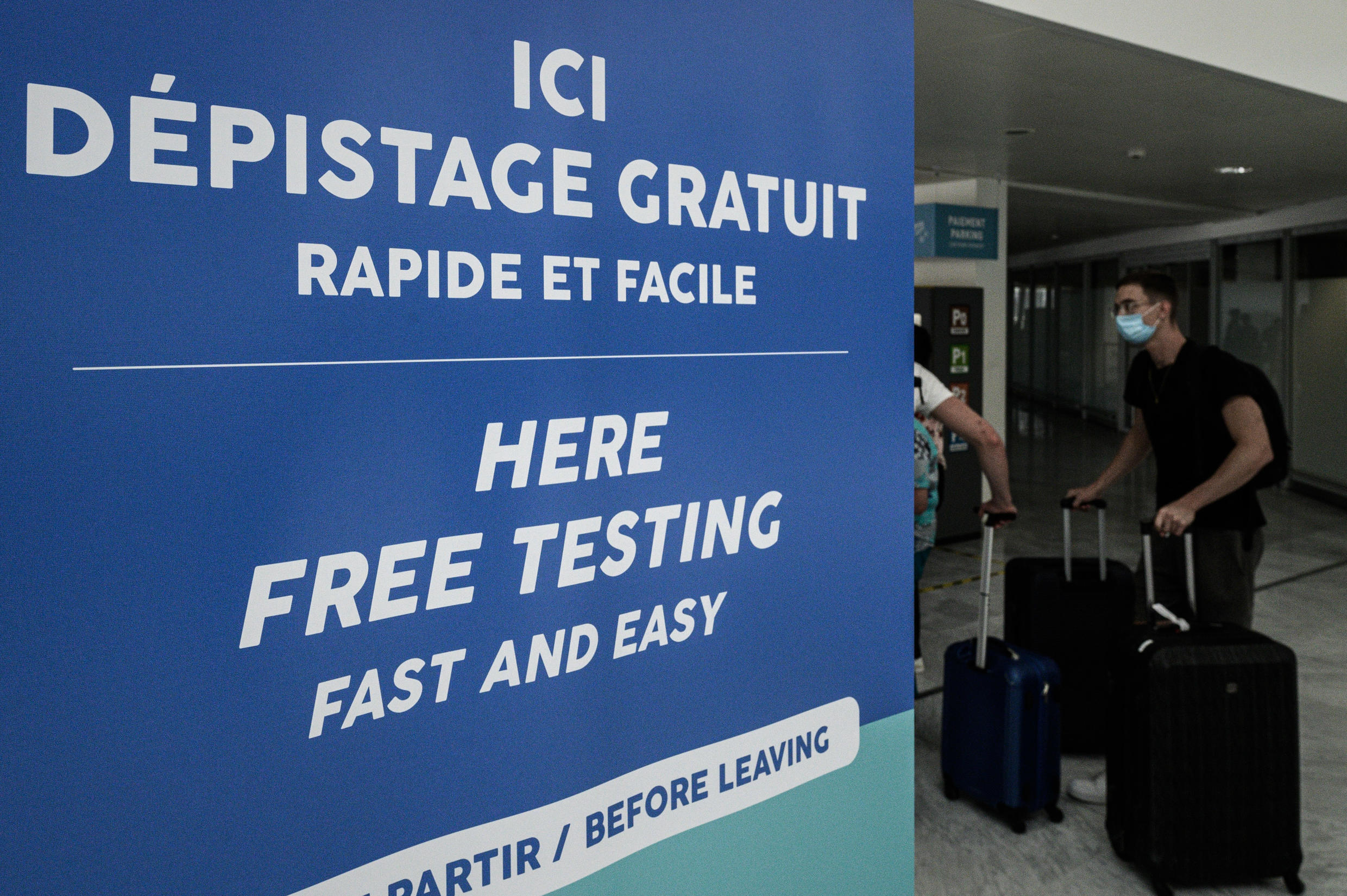 Passengers walk past a sign for free Covid-19 testing at the Bordeaux-Merignac Airport in Merignac, southwestern France, on July 23, 2020.