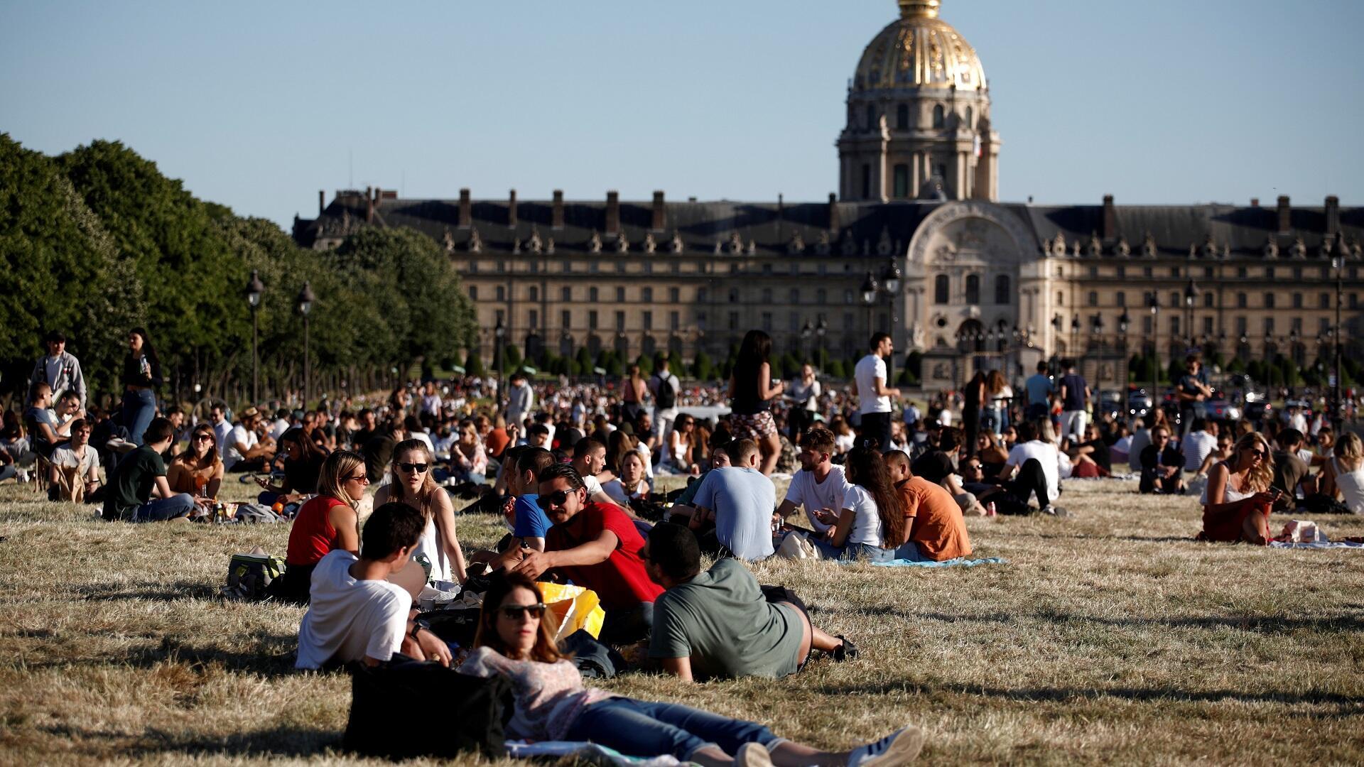 أشخاص يستمتعون بأشعة الشمس في حديقة صرح الأنفاليد بالعاصمة الفرنسية باريس، 29 مايو/أيار 2020.