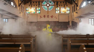 A worker disinfects a church in Wuhan, where the new coronavirus emerged late last year