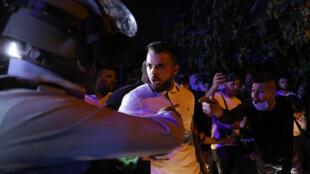 أحد المعتصمين الفلسطينيين في حي الشيخ جراح في القدس الشرقية المحتلة يجادل جندي من حرس الحدود الإسرائيلي خلال احتجاج في الحي في الخامس من أيار/مايو 2021 ضد إخلاء عائلات فلسطينية لصالح الجمعيات الاستيطانية