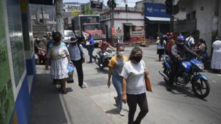 Guatemaltecos transitan las calles con máscaras faciales como medida preventiva contra la propagación del coronavirus en Amatitlan, 35 km al sur de Ciudad de Guatemala, el 13 de abril de 2020