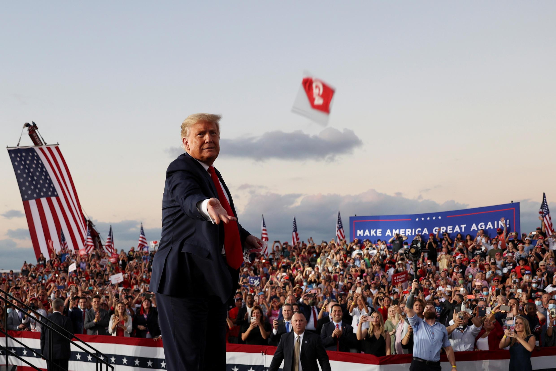 El presidente de Estados Unidos, Donald Trump, lanza una mascarilla facial desde el escenario durante un mitin de campaña, el primero que realiza desde que recibió tratamiento por el Covid-19. En el Aeropuerto Internacional Orlando Sanford, en Sanford, Florida, EE. UU., el 12 de octubre de 2020.