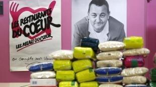 Paquets de riz devant une affiche de Coluche pour les Restos du Coeur