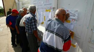 Ciudadanos verifican la información en una mesa de votación durante la jornada de elecciones regionales para nuevos gobernadores en Maracaibo.