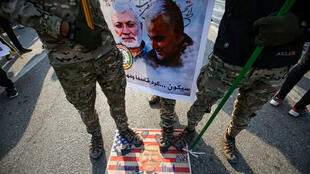 Members of the Hashed al-Shaabi paramilitary force step on a makeshift US flag bearinga caricature of President Donald Trump during the funeral procession of Iraqi paramilitary chief Abu Mahdi al-Muhandis (poster-L) , Iranian military commander Qasem Soleimani (poster-R), and eight others in the capital Baghdad's district of al-Jadriya, near the high-security Green Zone, on January 4, 2020.