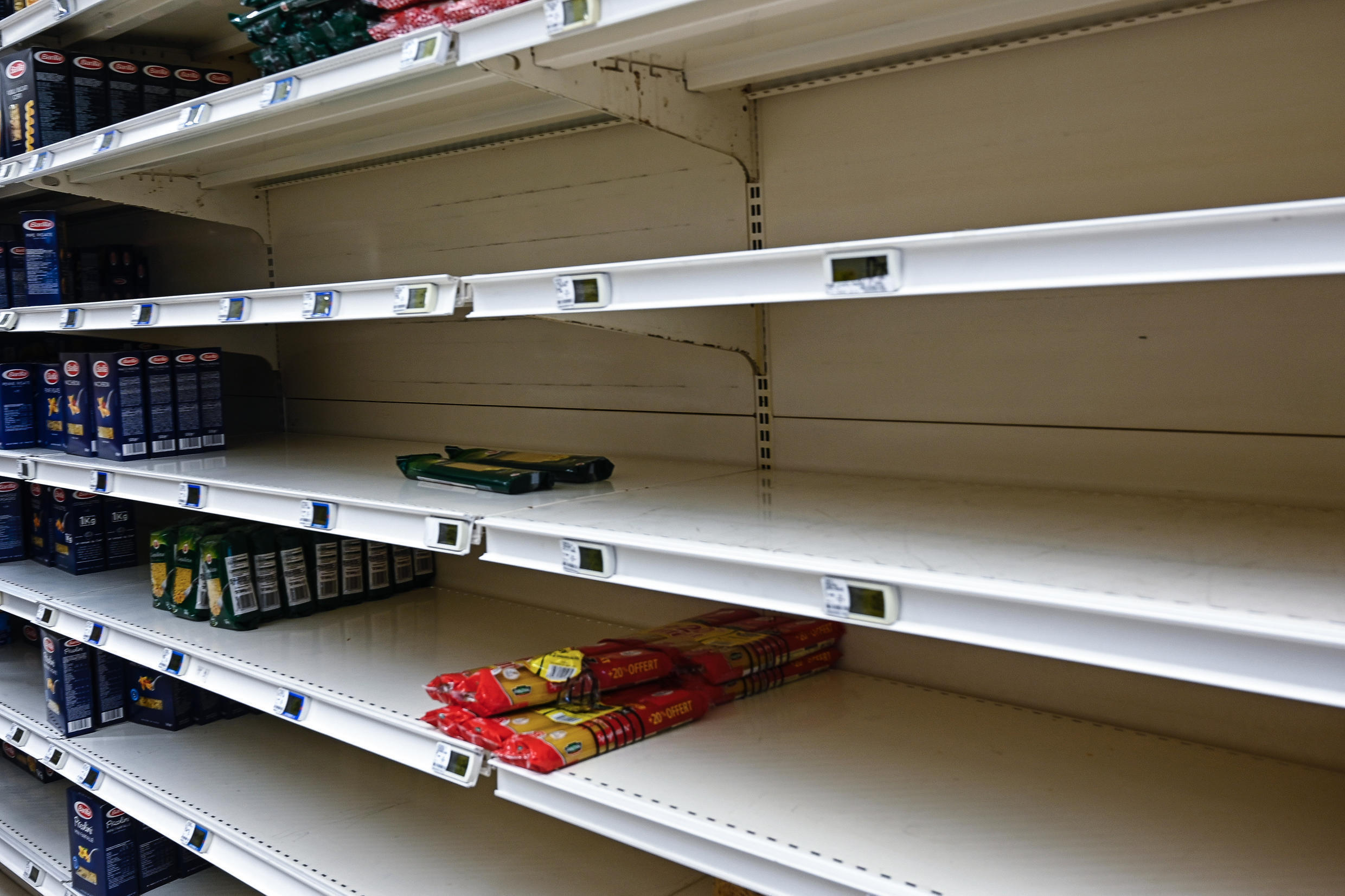 This picture taken on March 14, 2020, shows almost empty aisles in a supermarket in Tinteniac, about 30 kilometres from Rennes in western France.