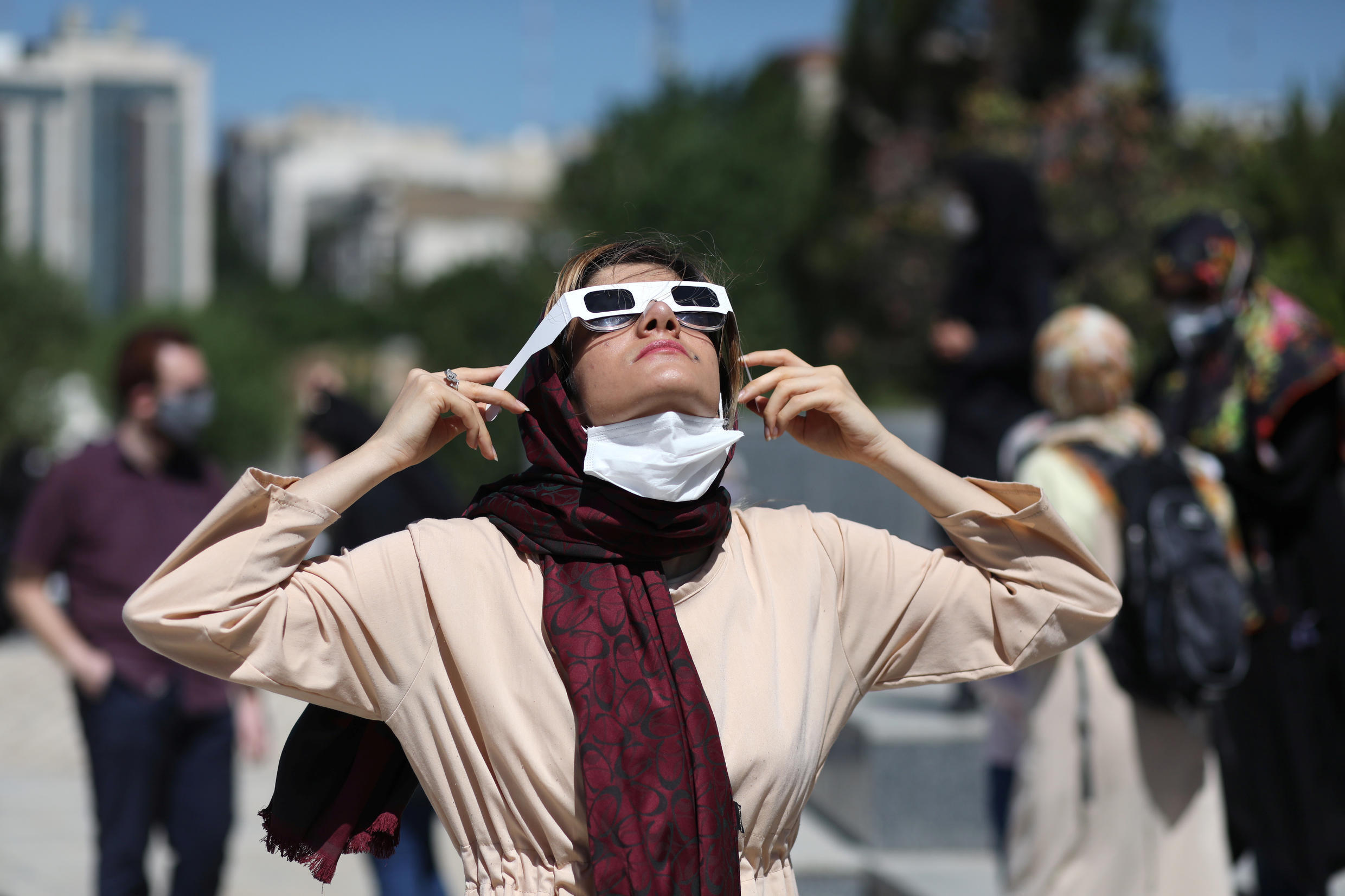 An Iranian woman uses special protective glasses to observe the solar eclipse, in Tehran, Iran, on June 21, 2020.