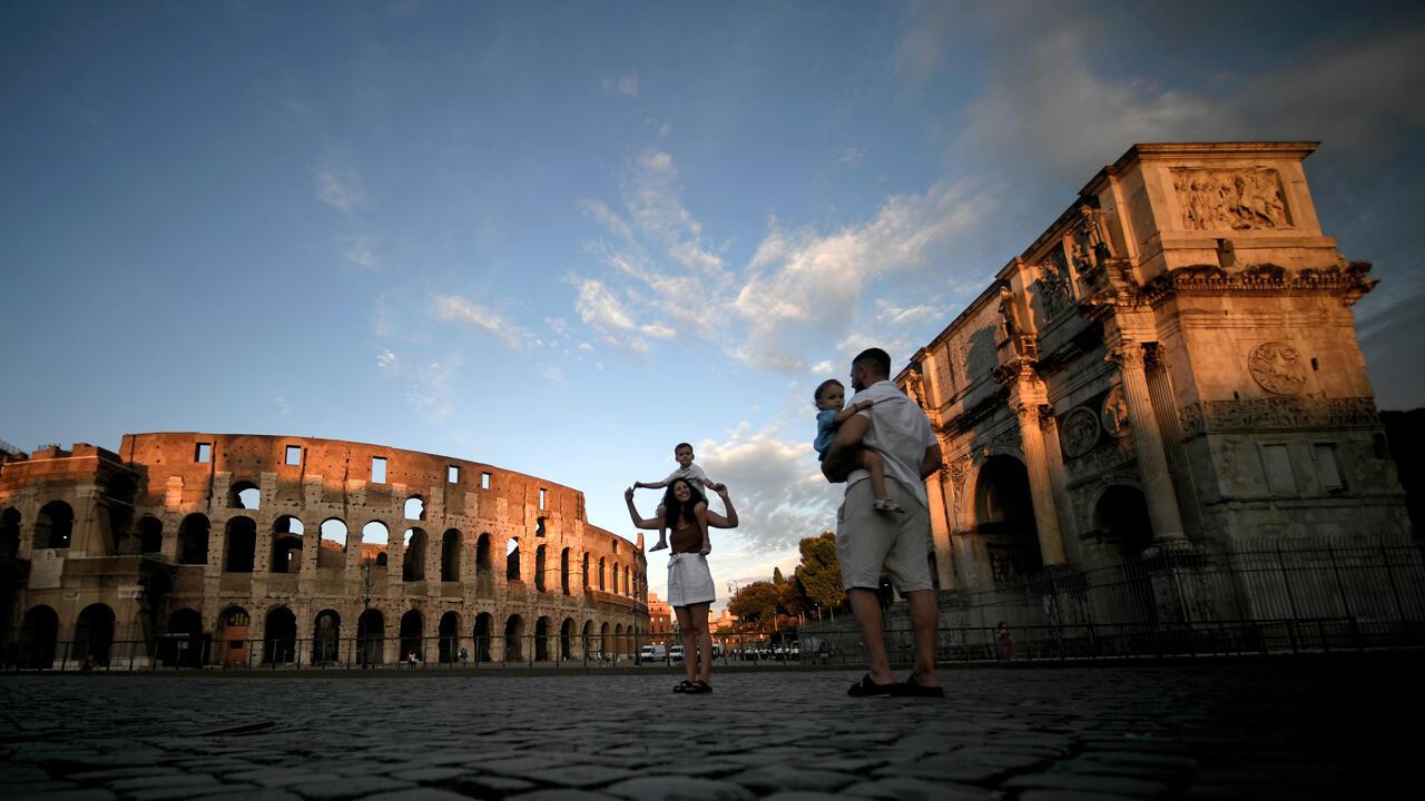 Una familia de turistas toma fotos junto al Arco de Constantino junto al Coliseo en el centro de Roma, el 17 de julio de 2020.