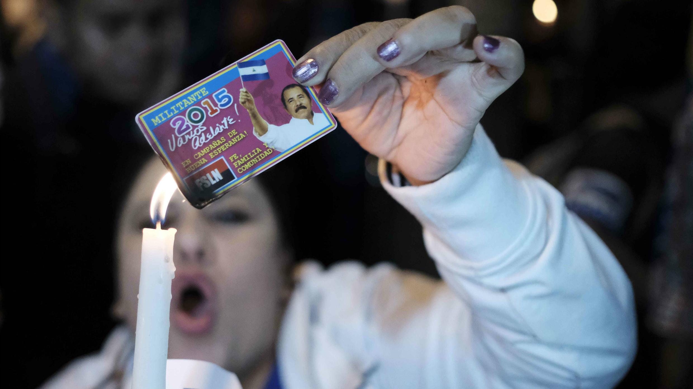 Mujer quema una imagen del presidente Daniel Ortega durante la vigilia por los más de 200 fallecidos en las protestas en Nicaragua. 21 de junio de 2018.