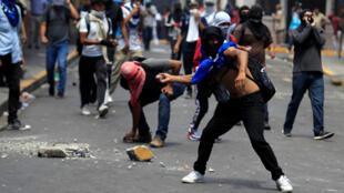 Los manifestantes arrojan piedras a la policía antidisturbios durante una protesta contra el presidente Juan Orlando Hernández, en Tegucigalpa, Honduras, el 6 de agosto de 2019.