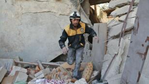 Un volontaire de la défense civile syrienne, plus connue sous le nom de Casques blancs, fait des recherches dans un bâtiment effondré de la Ghouta orientale le 28 novembre 2017.
