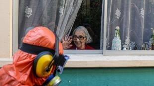 Una mujer saluda a un trabajador de la ciudad vestido con un traje de materiales peligrosos mientras desinfecta las calles de su vecindario como medida de precaución contra la propagación del nuevo coronavirus, en Santiago, Chile, el miércoles 15 de abril de 2020.