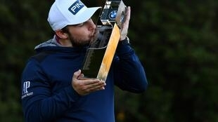 England's Tyrrell Hatton, wearing a hoodie, kisses the PGA Championship trophy after his victory at Wentworth Golf Club in Sunday