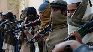 Former Afghan Taliban fighters holding weapons before they hand them over as part of a government peace and reconciliation process at a ceremony in Jalalabad on February 8, 2015.