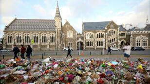 Personas caminan junto a las flores y homenajes que se muestran en memoria de las víctimas de la masacre de las mezquitas gemelas frente al Jardín Botánico de Christchurch. 29 de marzo de 2019.