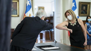 President Sebastian Pinera greets his new Minister for Women Macarena Santelices with an elbow bump at the presidential palace in Santiago, Chile