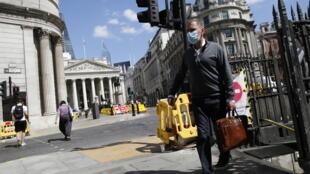 Un transeúnte con mascarilla sale del metro con mascarilla cerca del Banco de Inglaterra, en la City de Londres, el 17 de julio de 2020