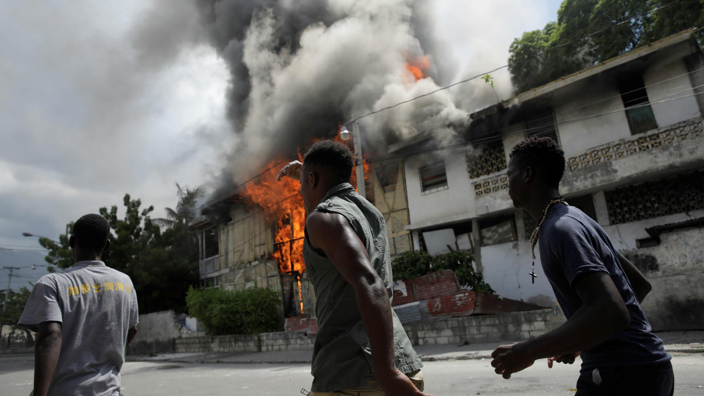 Los manifestantes pasan por un edificio en llamas durante una manifestación convocada por los partidos de la oposición y la sociedad civil para protestar contra el gobierno en Puerto Príncipe, Haití, el 9 de junio de 2019