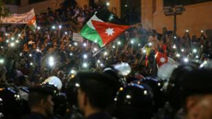 لجأ المتظاهرون إلى رفع الأعلام الأردنية وأضاؤوا مصابيح هواتفهم المحمولة بمواجهة ضباط شرطة أردنيين أثناء احتجاجات ليلية بالقرب من مكتب رئيس الوزراء في عمان، في 5 حزيران/يونيو 2018.