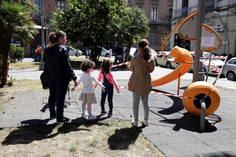 Mujeres y niños se paran frente a un parque cerrado, mientras Italia comienza un desconfinamiento gradual de las cuarentenas impuestas por la propagación de la enfermedad por coronavirus (Covid-19) en Catania, Italia, el 5 de mayo de 2020.
