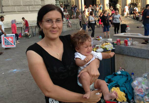 Amira and her 4-month-old son Fawaz, from Syria, outside Keleti train station in Budapest. (Photo: Fernande van Tets)