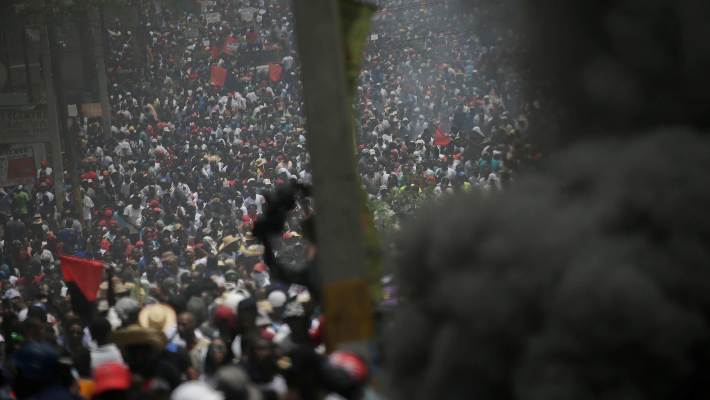 Los manifestantes pasan por un edificio en llamas durante una manifestación convocada por los partidos de la oposición y la sociedad civil para protestar contra el Gobierno en Puerto Príncipe, Haití, el 9 de junio de 2019.