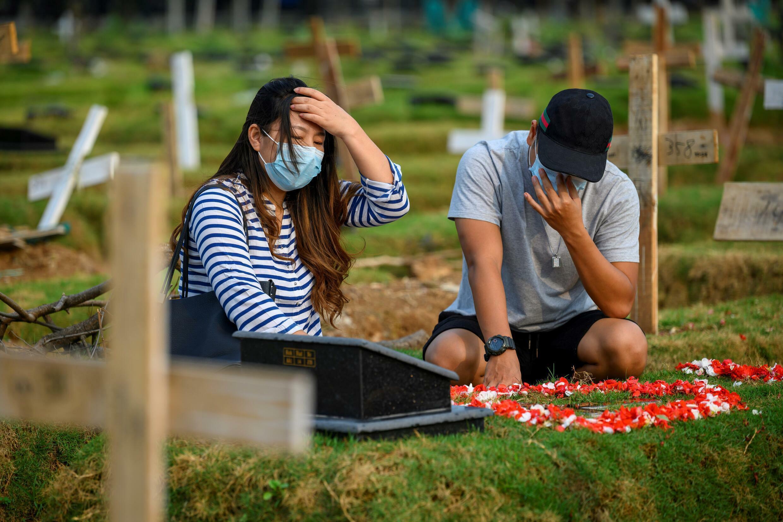 Tirzah Manitic (kiri) dan Eric Alexander (kanan) di makam anak mereka yang meninggal karena penyakit Pemerintah-19 di Jakarta pada 1 Agustus 2021.
