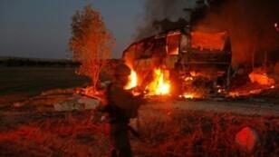قوات أمن إسرائيلية وعناصر إطفاء قرب حافلة تحترق بعد إصابتها بصاروخ أطلق من قطاع غزة في 12 تشرين الثاني/نوفمبر 2018