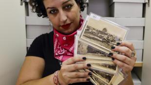 """Sachar Knaani, chercheuse à l'Université hébraïque tient des cartes de la collection """"Cartes postales de la Palestine"""" à l'université de Jérusalem le 24 septembre 2020"""