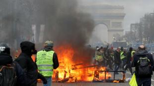 """Una barricada en llamas se ve durante una manifestación del movimiento """"chalecos amarillos"""" en París, el 16 de marzo de 2019."""