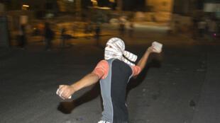 Un jeune Palestinien visant des agents de police israélienne le 27 juillet 2010.