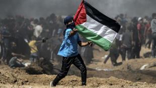 Un manifestant agite un drapeau palestinien le long de la fronitère entre Gaza et Israel, le 8 juin 2018