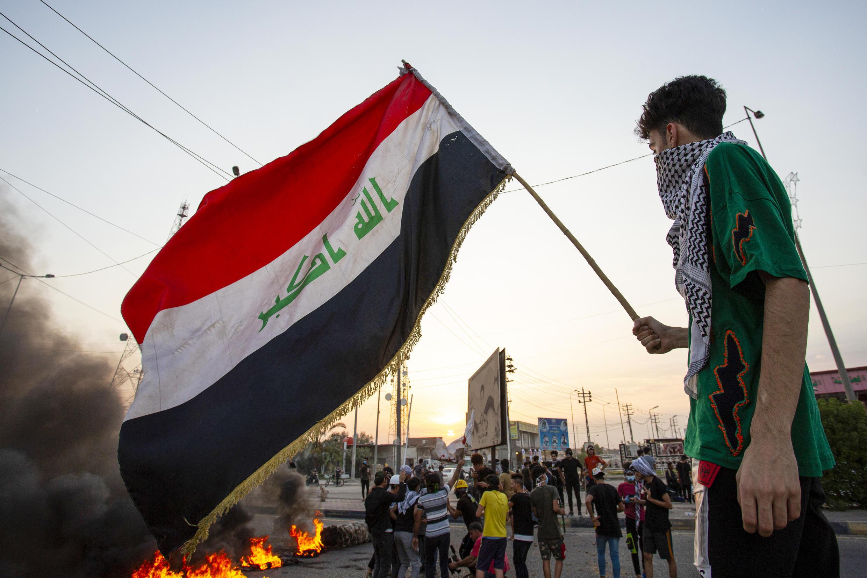 متظاهر يلوح بالعلم العراقي في البصرة بتاريخ 14 تموز/يوليو 2020