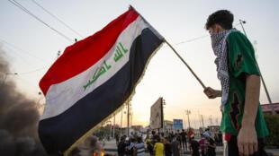 متظاهر يلوح بالعلم العراقي