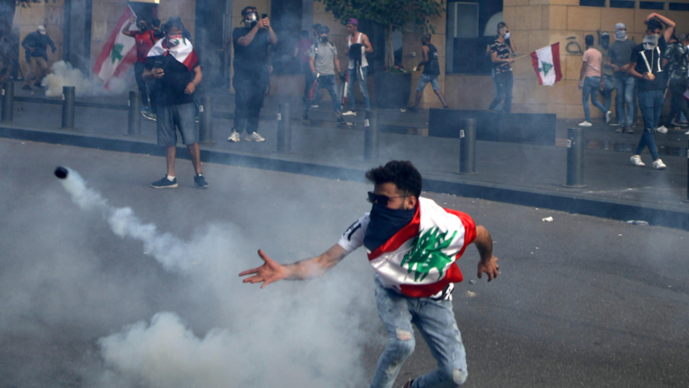A Lebanese protester throws back a tear gas canister amid clashes with riot police following a demonstration in central Beirut, on June 6, 2020.