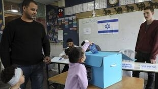 An Arab-Israeli girl casts her father's ballot for the parliamentary election at a poling station in the Bedouin town of Rahat near the southern Israeli city of Beersheba on March 2, 2020.