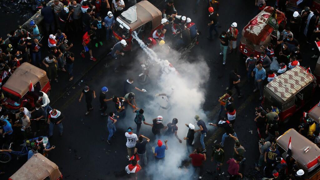 Los manifestantes intentan sacar un bote de gas lacrimógeno durante una protesta contra el gobierno en Bagdad, Irak, 30 de octubre de 2019.