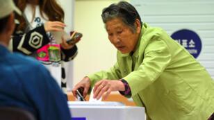 Une femme dépose son bulletin dans une urne électorale dans un bureau de vote de Séoul, le 9 mai 2017..