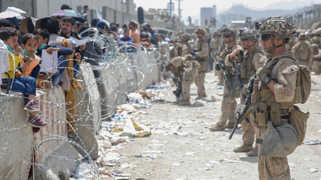 Varios soldados de la OTAN vigilan a ciudadanos afganos en el aeropuerto de Kabul. El 20 de agosto de 2021.
