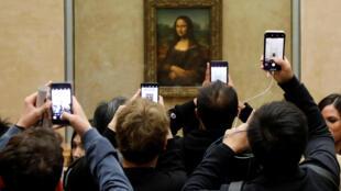 """Los visitantes toman fotos de la pintura """"Mona Lisa"""" (La Gioconda) de Leonardo Da Vinci en el Museo del Louvre en París, Francia, 3 de diciembre de 2018. Fotografía tomada el 3 de diciembre de 2018."""