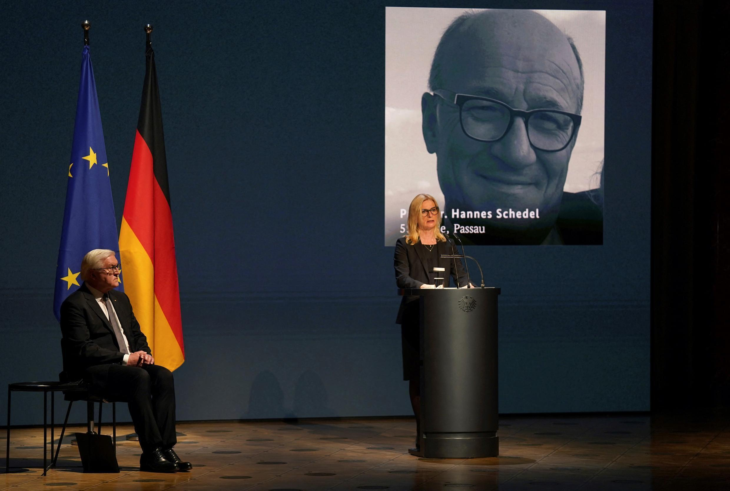 German President Frank-Walter Steinmeier listens as Anita Schedel, widow of the doctor Hannes Schedel of Passau, who died of the coronavirus, delivers a speech during a ceremony for the German victims of the pandemic at the Konzerthaus concert hall in Berlin on 18 April 2021.