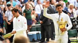 El serbio Novak Djokovic saluda mientras sostiene su trofeo de campeón, junto al suizo Roger Federer, después de la final de Wimbledon. Londres, Reino Unido. 14 de julio de 2019.