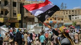 يمني يرفع علم بلاده تنديدا بالنزاع المسلح في بلاده في تعز في 17 نيسان/أبريل 2016