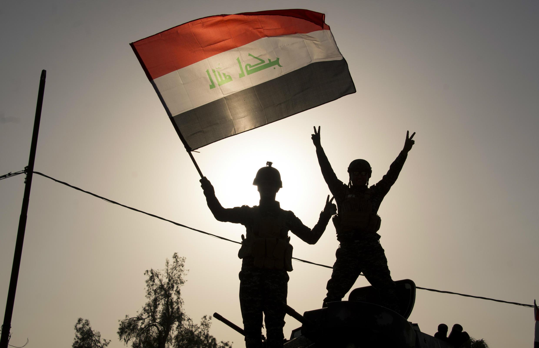 Des membres des forces irakiennes brandissent le drapeau irakien et font le signe de la victoire, après la libération de Mossoul, le 9 juillet 2017.
