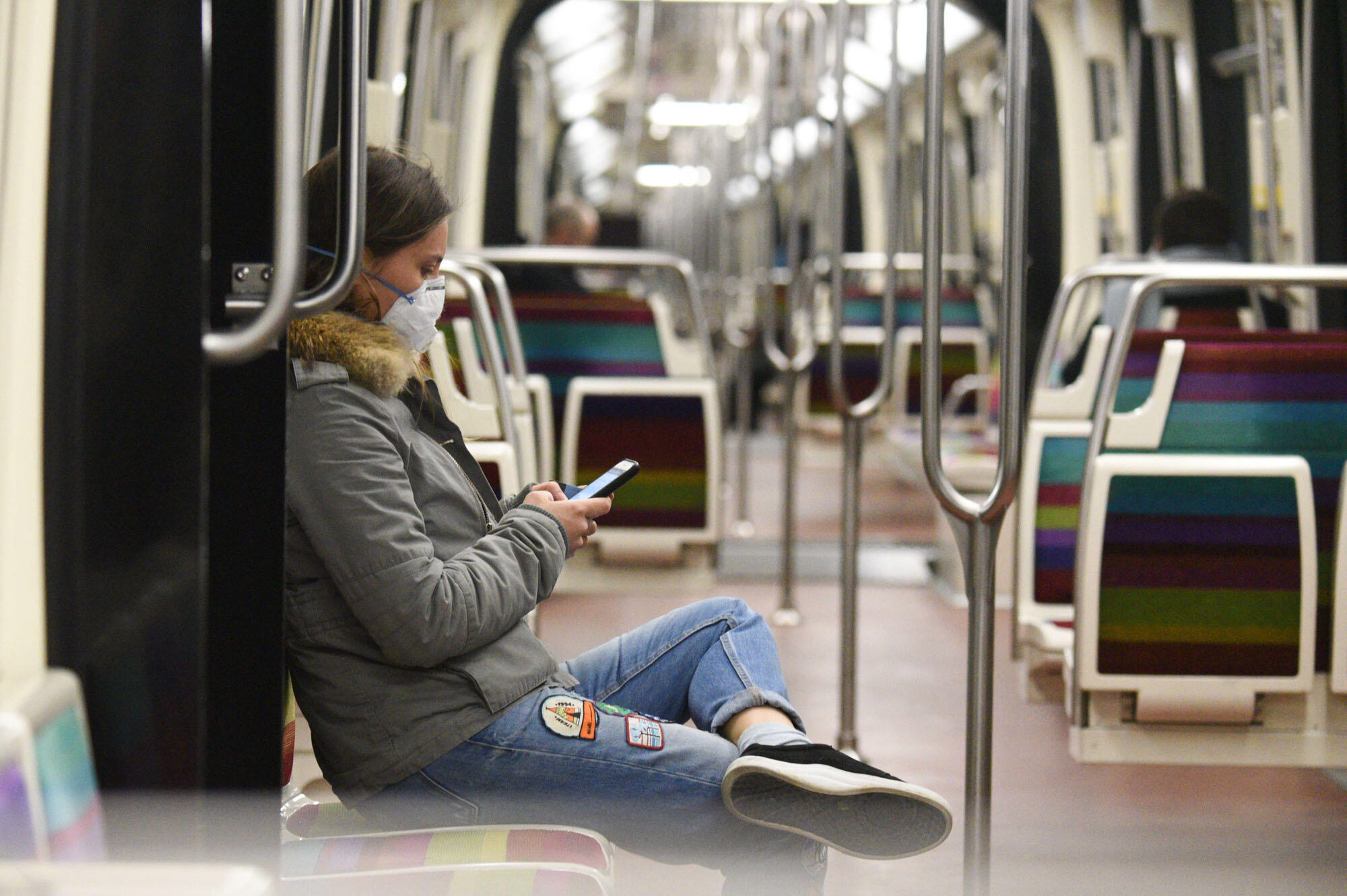 A woman with a protective mask sits alone in the Parisian metro. Metro, bus and tram services in Paris have been severely curtailed but are still functioning during the lockdown.
